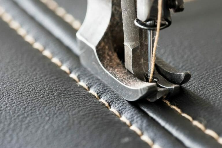 Leathercraft, sewing machine producing customized leather products in France, needle inside black leather, golden thread. picture is showing how to sew high-quality leather