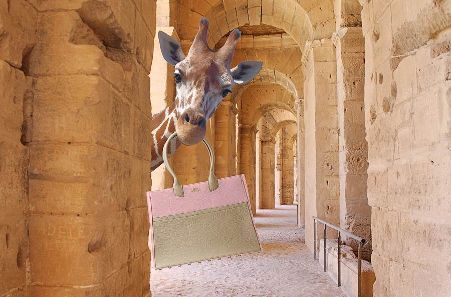 Beige pink leather tote in Sophies (giraffe) mouth. Giraffe looks around a pilar into camera