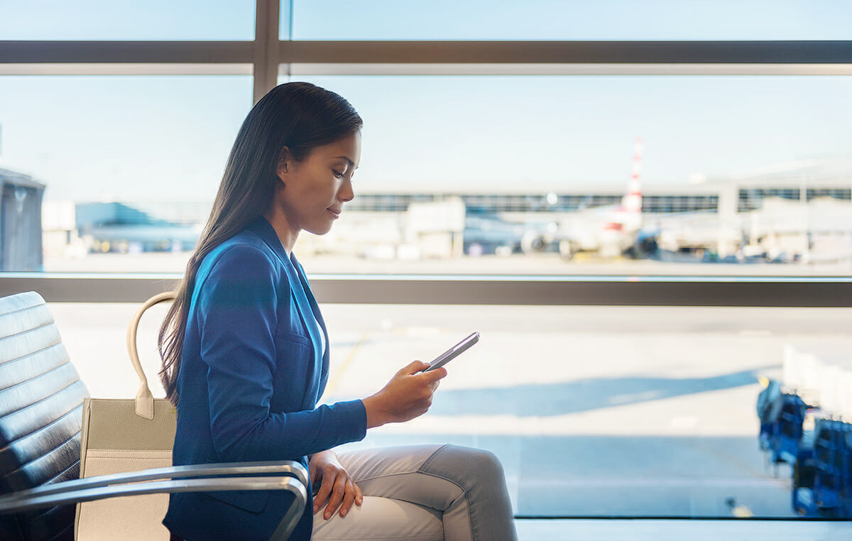 Business woman on phone while sitting on airport waiting for packing intelligently