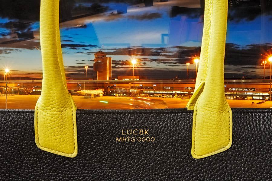 Luxury leather handbag in yellow and black leather in front of Zurich airport.