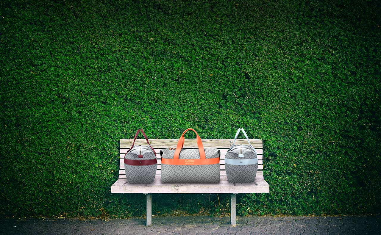 Exclusive handcrafted luxury leather bags and accessories, 3 weekender duffles stand on a bench in front of a green bush