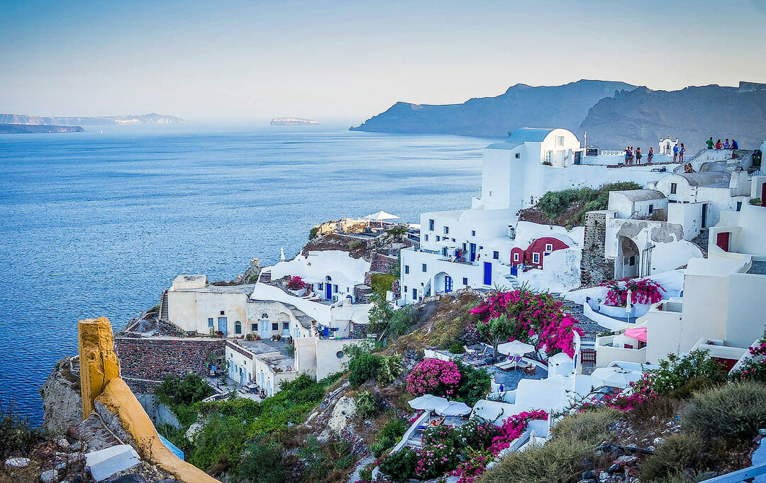 Greece island at Mediterranean Sea, white houses with blue doors and behind the sea