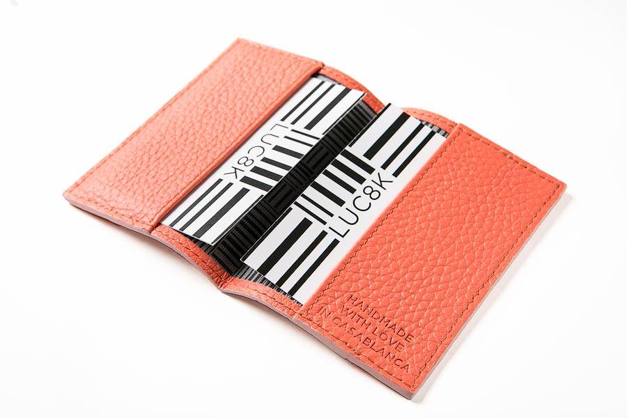 Handcrafted custom business card holder opened on white background, with business cards in pouches from the company Luc8k