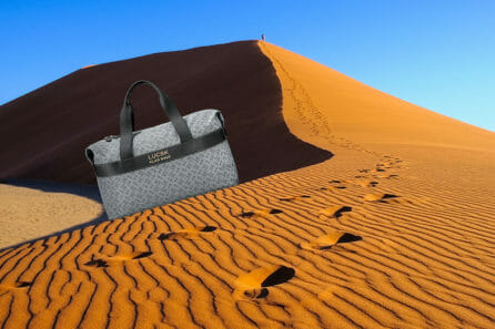 Handmade duffle weekender bag stands on red sand dune. The new reimagining luxury