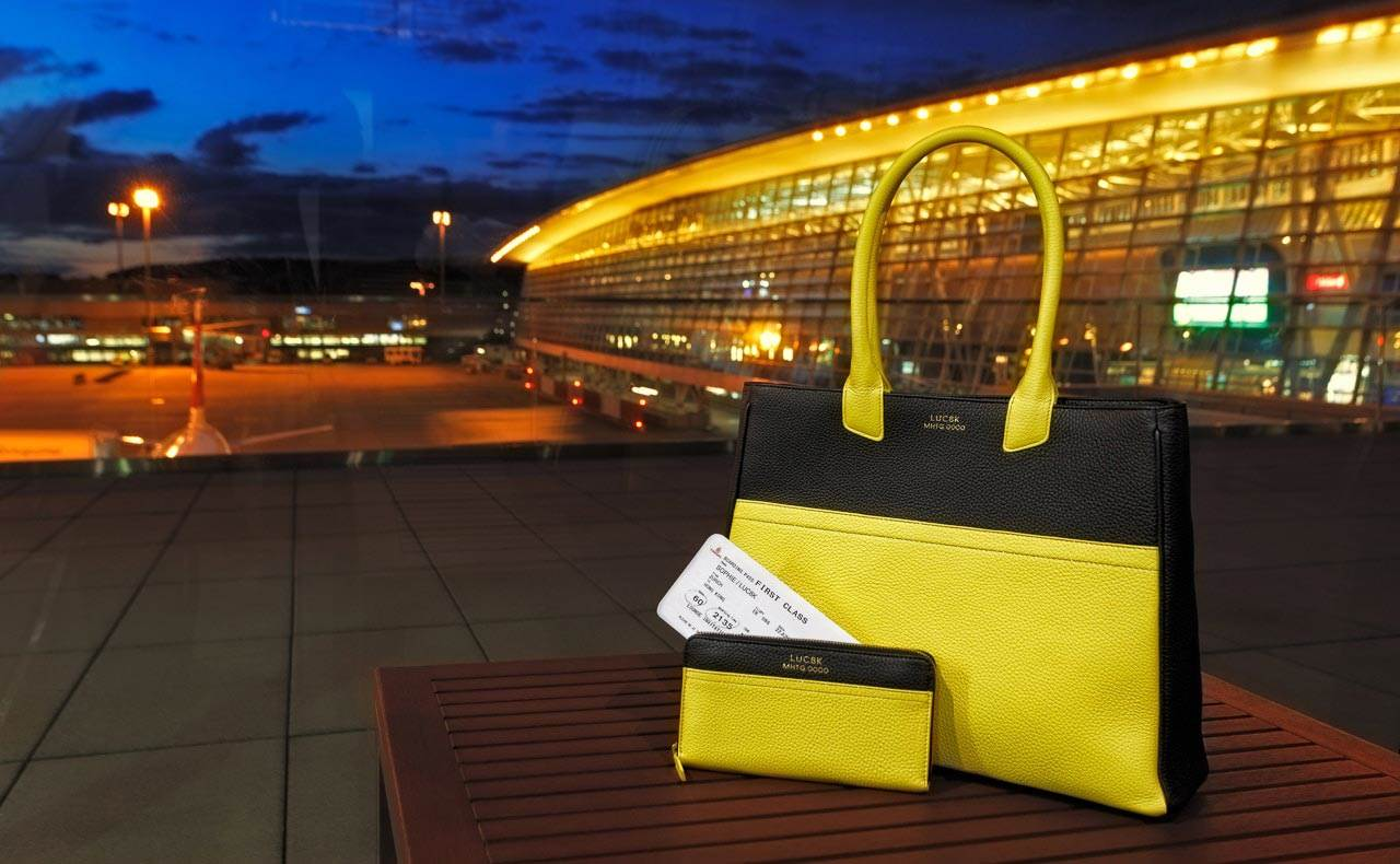 Exclusive handcrafted luxury leather bags, handmade leather Tote bag and custom leather wallet standing on a table, behind airplane and airport building