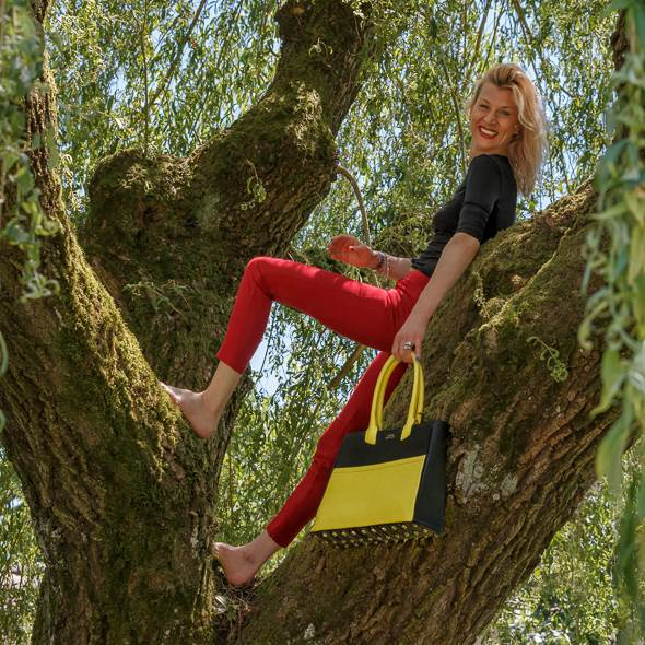 Founder of handcrafted luxury leather bags and accessories of LUC8K Karen Olivo in a tree with a leather Tote bag