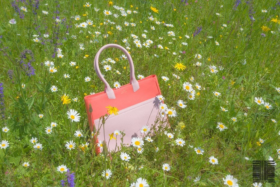 high quality leather goods, a custom handmade leather tote reclining in a field of flowers. Color of leather Tote bag red pink