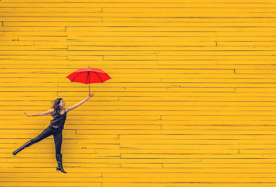 Woman jumping in sophisticated style happily with umbrella in her hand, behind yellow wood wall