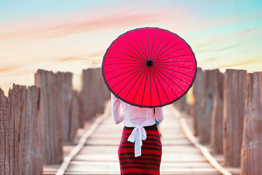 Sophisticated style, dressed in red and white shirt, red umbrella, woman walking along a pier at a lake