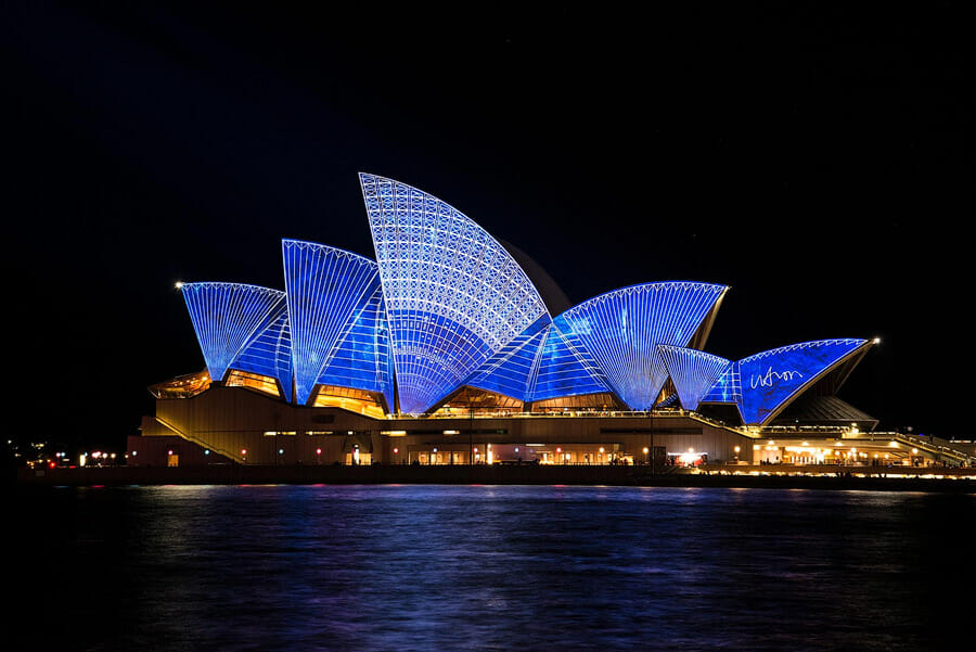 Handbags for ladies, Sydney Opera house roofs lit up in blue, in front water, behind black sky