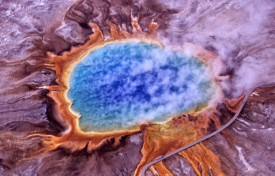 Bird view of a thermal spring in yellowstone national park. Very colourful blue water, smoke and red color ground around it