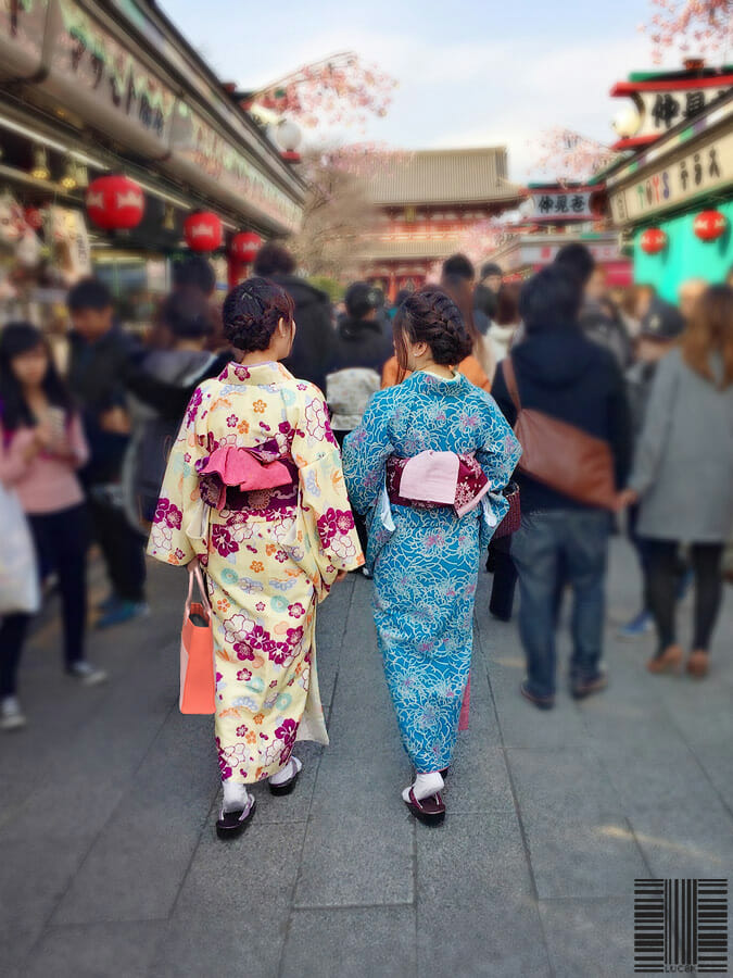 Two Japanese women walking with a custom fashion leather bag on a road