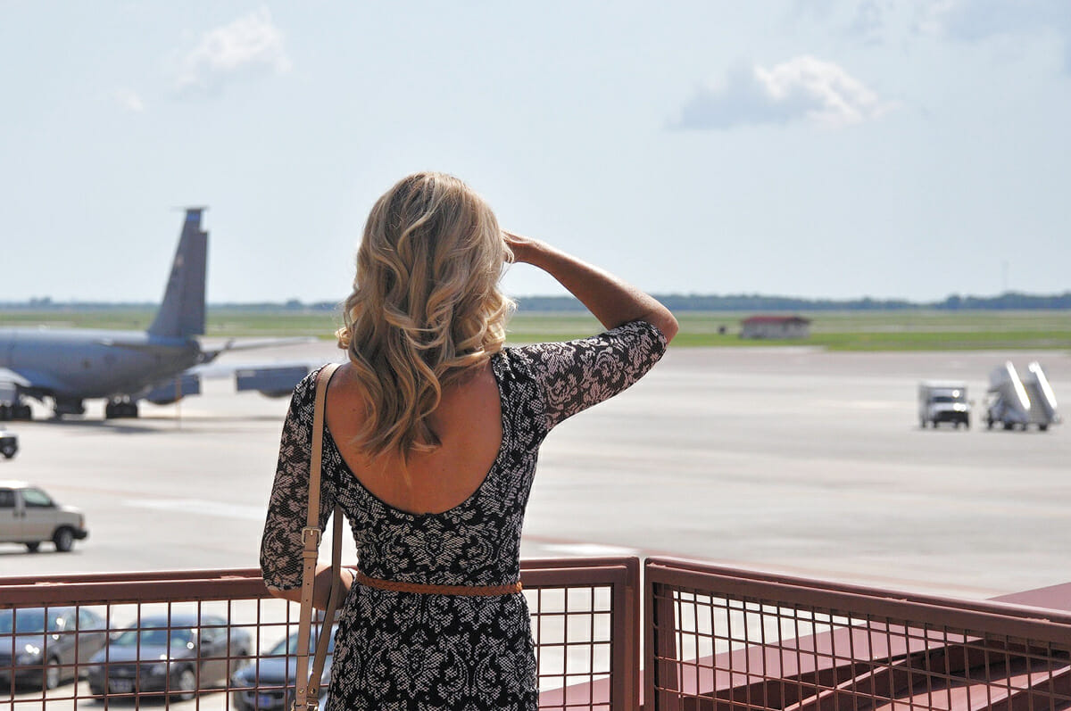 real woman observing the take off planes at airport. Woman looks over the landing strips, airplane behind her