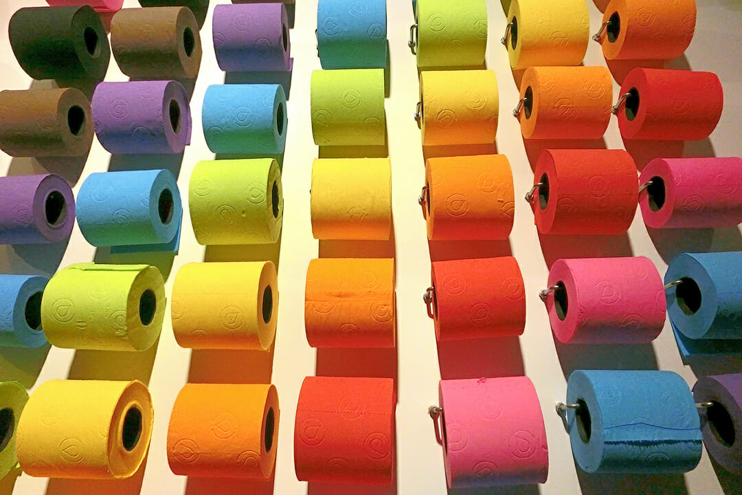 Colourful toilet paper rolls hanging on a wall. Sophie travels home, she might need a roll